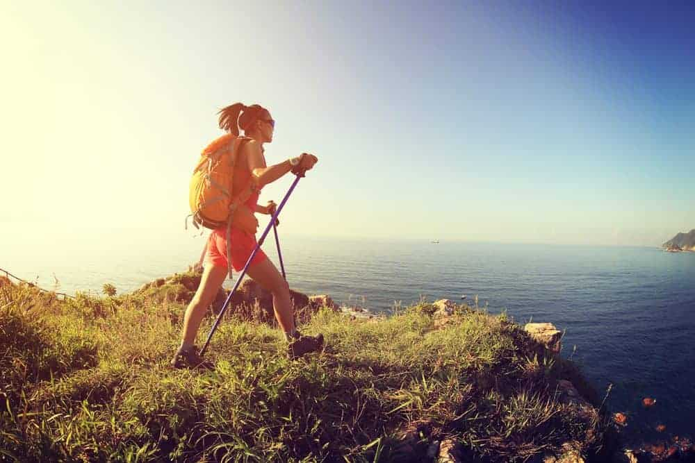 Female Two Walking Poles View over Ocean on Mountain